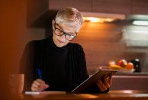 Frau mit Tablet arbeitet in der Küche