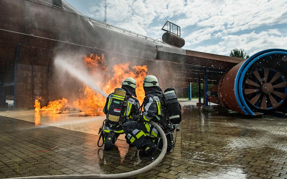 Feuerwehrübungsplatz: Zwei Feuerwehrmänner beim Löschen