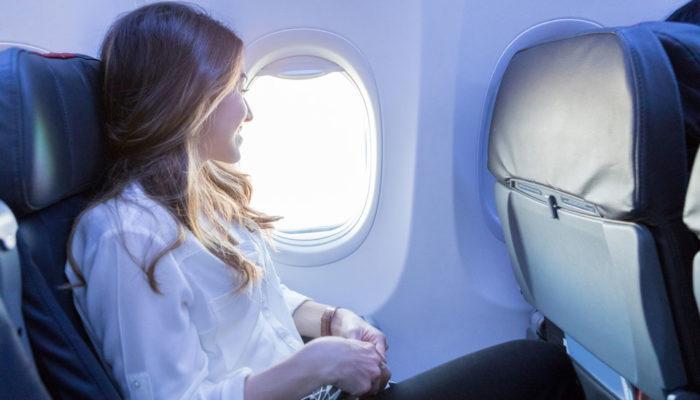 Junge Frau sieht im Flugzeug aus dem Fenster
