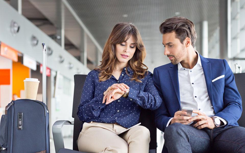 Mann fragt Frau nach Uhrzeit am Flughafen