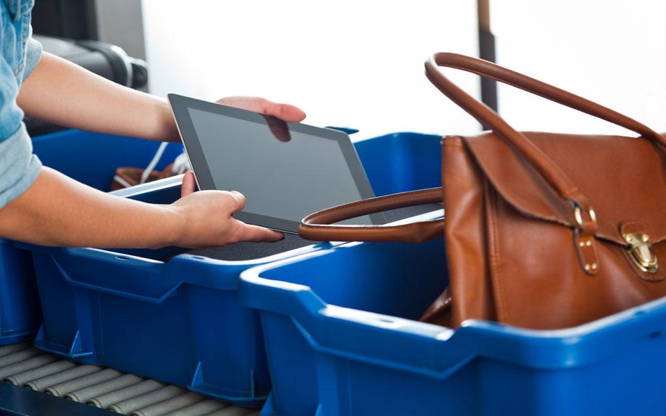 Tablet wird aus Ablage am Sicherheitscheck entnommen