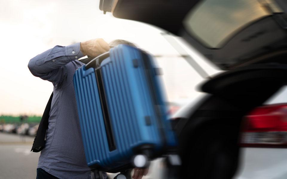 Mann wuchtet Koffer ins Auto