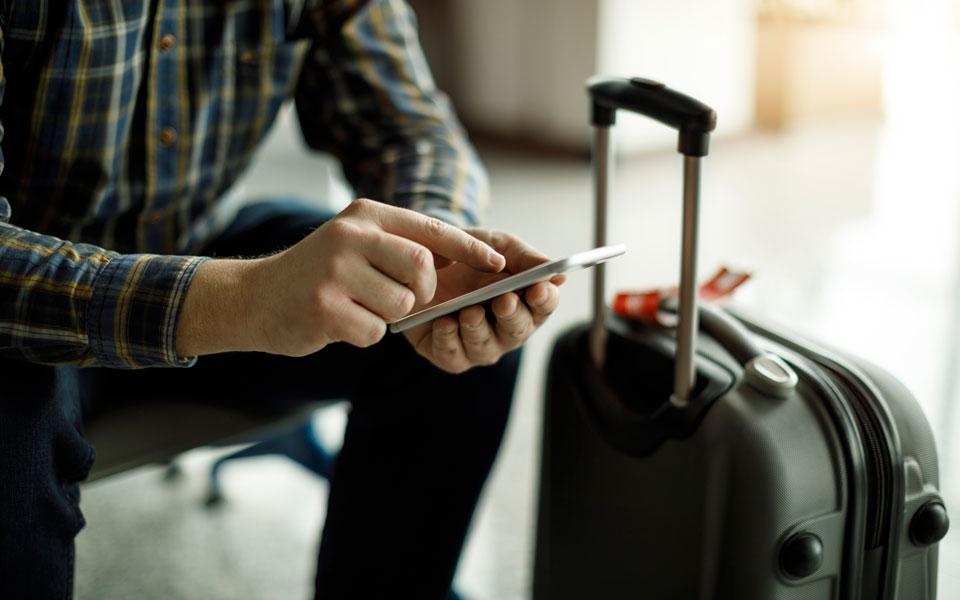 Reisender tippt auf Smartphone