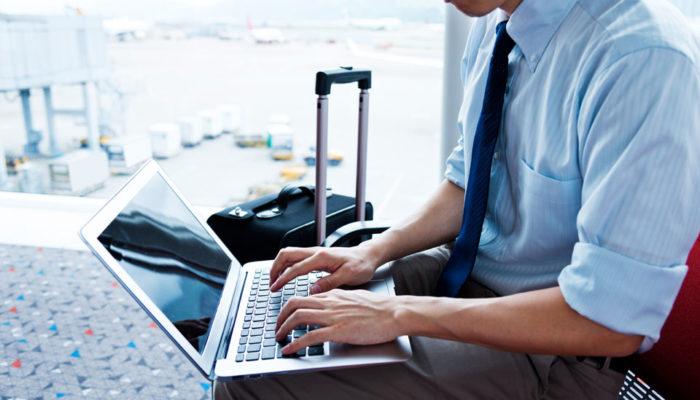 Geschäftsreisender schreibt auf Notebook am Flughafen
