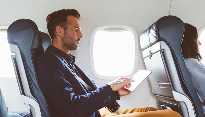 Mann mit Tablet im Flugzeug