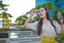 Asiatin mit Kopfhörer tanzend