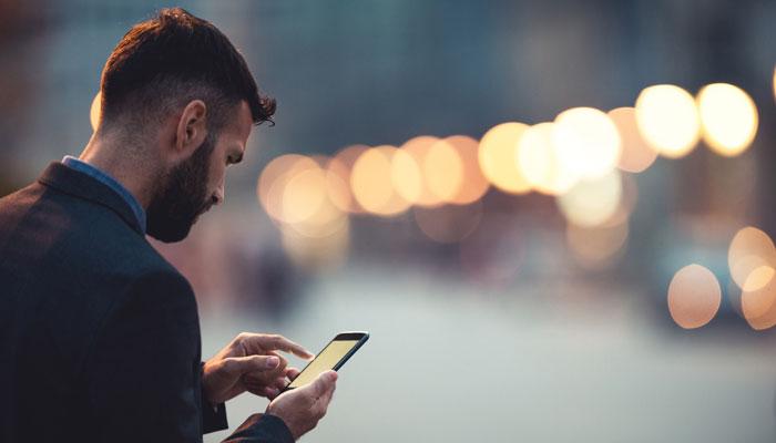 Mann auf Straße mit Smartphone