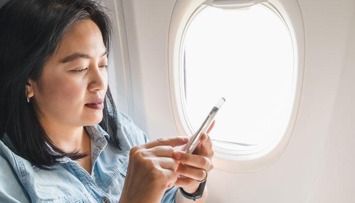 Asiatin im Flugzeug mit Smartphone