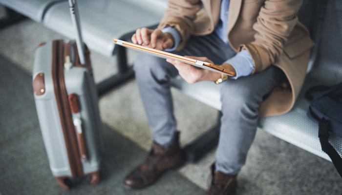 Geschäftsmann mit Koffer und Tablet