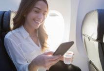 Frau mit Smartphone in Flugzeugkabine
