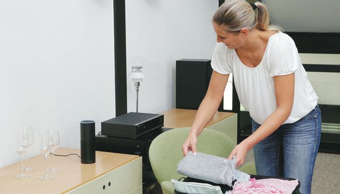 Frau packt Koffer und spricht mit Alexa