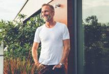 Mann im T-Shirt steht auf Balkon