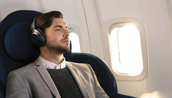 Business Traveller im Flugzeug mit Kopfhörer
