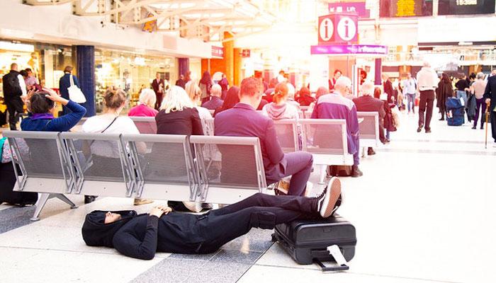 Mann mit Travel-Jumpsuit liegt auf Flughafen-Boden