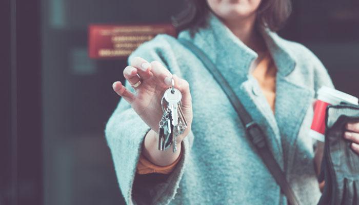 Frau mit Schlüssel in der Hand vor Haustür