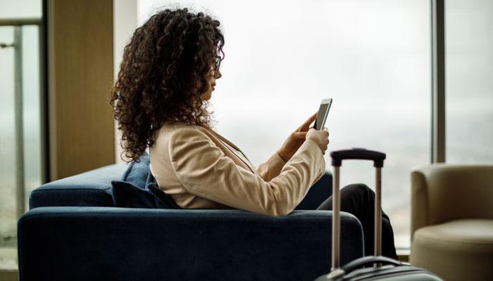 Frau sitzt mit Smartphone in Hotellobby