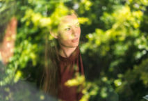 Frau hinter Baumspiegelung