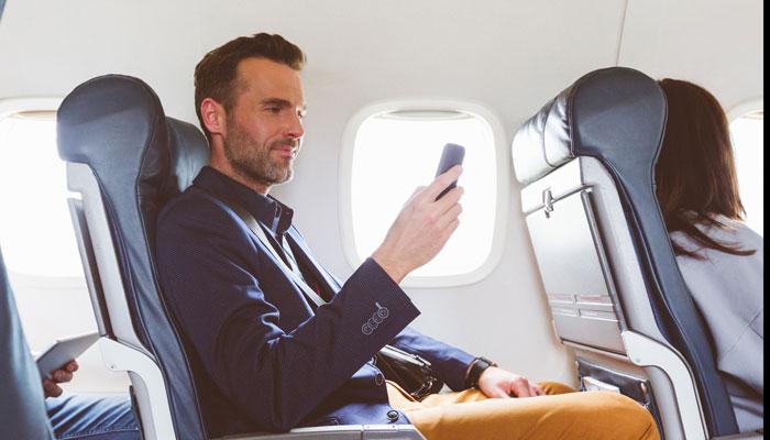 Mann im Flugzeug mit Smartphone; Foto: iStock.com/izusek