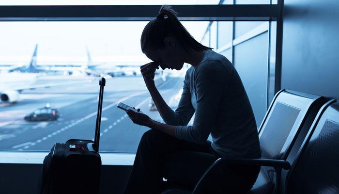 Frau reibt sich Stirn am Flughafen; Foto: iStock.com/kieferpix