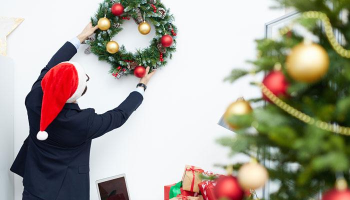 Mann im Anzug hängt einen weihnachtlichen Kranz auf, Foto: iStock.com/shironosov