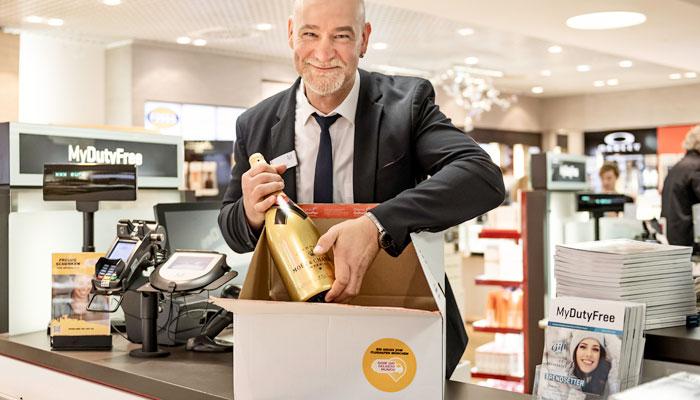 Verkäufer am Flughafen München verpackt eine Flasche; Foto: Flughafen München