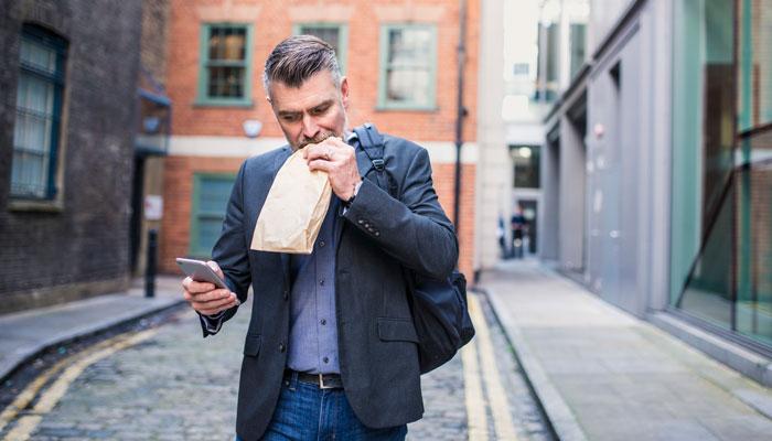 Mann mit Snacktüte und Smartphone; Foto: iStock.com/ AzmanJaka