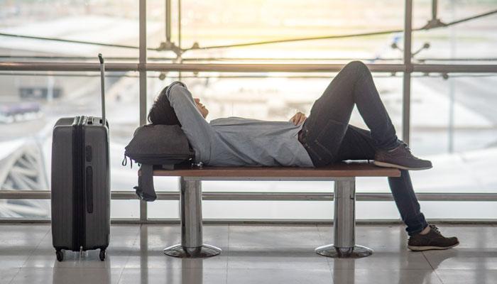 Mann liegt auf Bank am Airport; Foto: iStock.com/Zephyr18