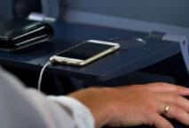 Mann sitzt im ICE, auf Tisch liegen Smartphone und Geldbeutel: Foto: iStock.com/ justhavealook