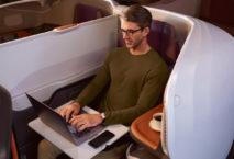 Mann sitzt in der Business Class in der A380 der Singapore Airlines und arbeitet am Notebook; Foto: Singapore Airlines