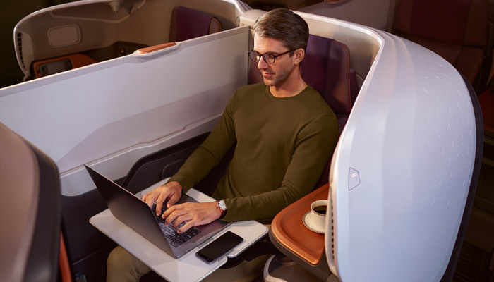 Mann sitzt in der Business Class in der A380 der Singapore Airlines und arbeitet am Notebook; Foto: Singapore Airlines