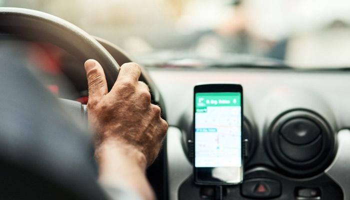 Autofahrer am Steuer mit Smartphone; Foto: iStock.com/PeopleImages