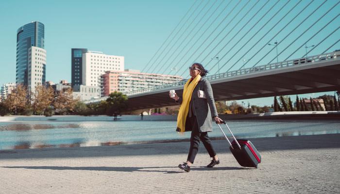 Frau mit Trolley spaziert durch Stadt; Foto: iStock.com/martin-dm