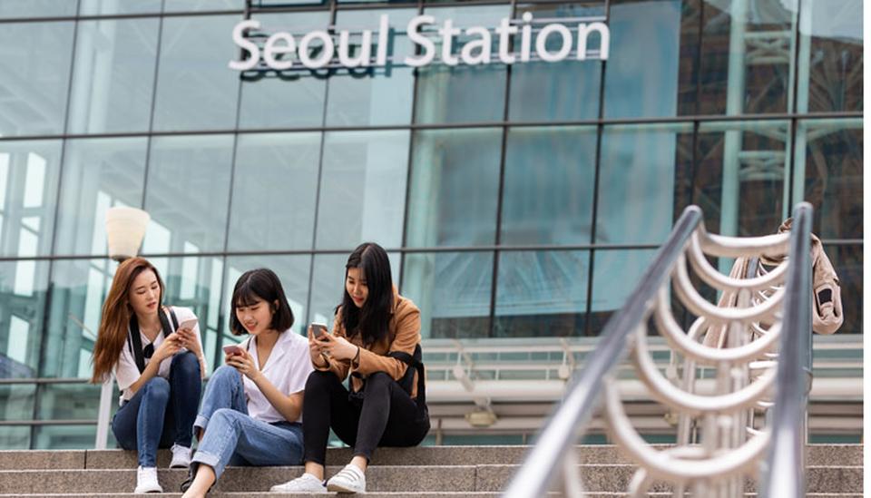 Drei junge Frauen mit Smartphones vor der Seoul Station; Foto: iStock.com/LeoPatrizi)
