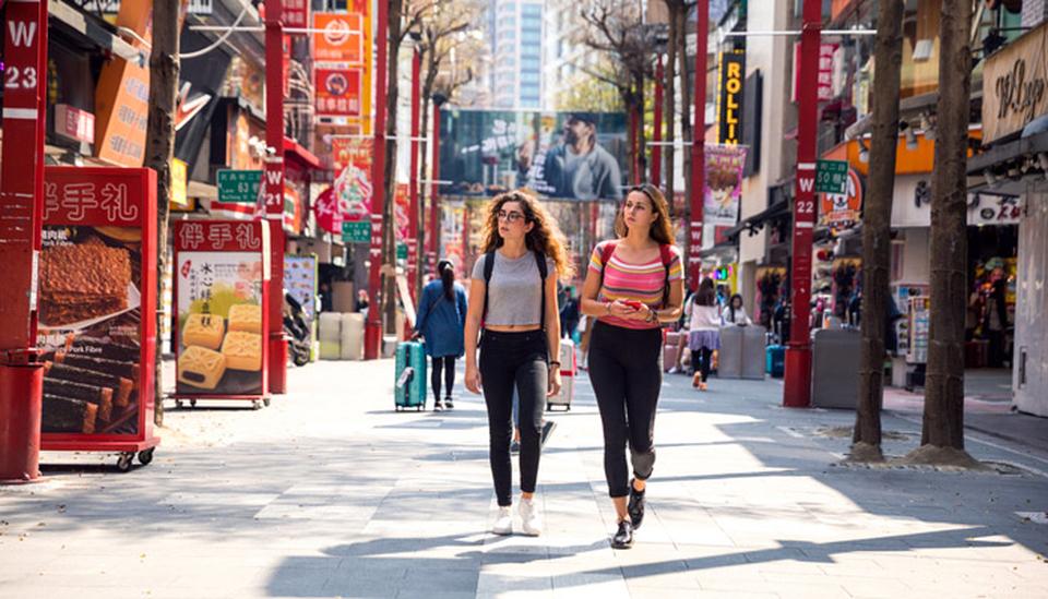 Zwei junge Frauen spazieren durch Taipeh; Foto: iStock.com/LeoPatrizi)