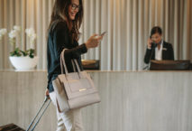 Frau mit Trolley geht mit Smartphone an Rezeption vorbei; Foto: iStock.com/jacoblund