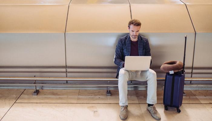 Mann sitzt mit Laptop am Flughafen; Foto: iStock.com/David Prado