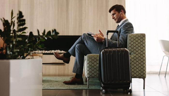 Geschäftsmann liest Magazin in Airport-Lounge; Foto: iStock.com/jacoblund