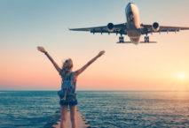 Frau streckt die Hände zum Himmel, während Flugzeug über sie fliegt; Foto: iStock.com/den-belitsky