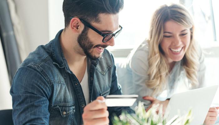 Junger Mann und junge Frau mit Kreditkarte vor Tablet; Foto: iStock.com/Georgijevic
