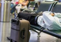 Mann im Anzug liegt auf Sitzbank im Flughafen; Foto: iStock.com/ SamuelBrownNG