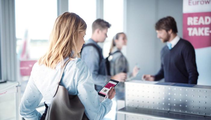 Frau mit Smartphone vor dem Boarding; Foto: Eurowings