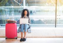 Frau mit pinkem Koffer sitzt im Terminal; ip einfach schöner! Foto: iStock.com/David-Prado