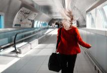 Frau mit wehendem Haar läuft über Rolltreppe am Flughafen; Foto: iStock.com/stock_colors