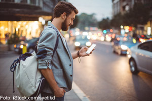 Mann mit Rucksack und Smartphone; Foto: iStock.com/Svetikd
