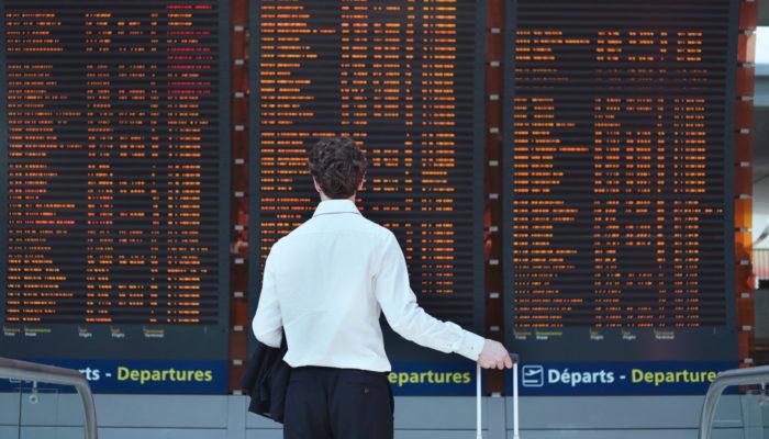 Geschäftsmann steht mit Trolley vor Anzeigentafel am Flughafen; Foto: Stock.com/anyaberkut