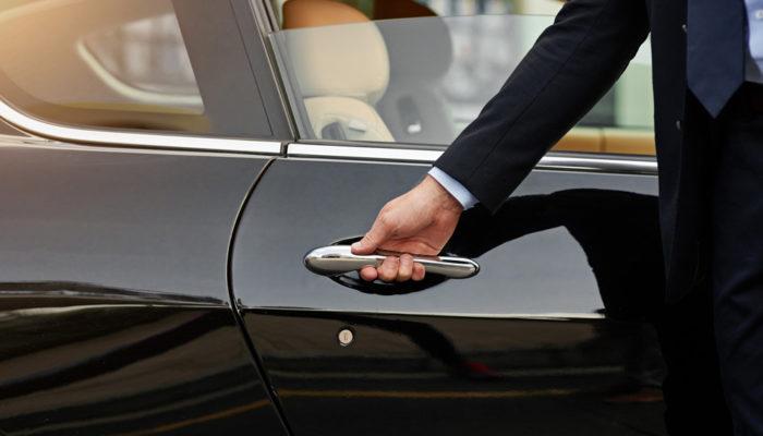 Chauffeur hält Tür von schwarzer Limousine; Foto: iStock.com/ PeopleImages