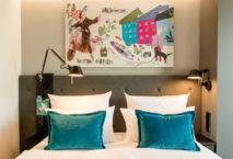 Coole Kunst über dem Bett: Blick in ein Zimmer im neuen Motel One München-Haidhausen. Foto: Motel One