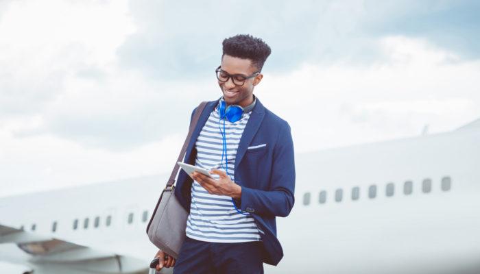 Junger Mann mit Kopfhörer und Tablet vor Flugzeug. Foto: iStock.com/izusek