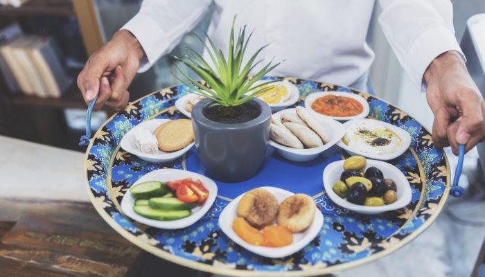 Mann serviert Platte mit orientalischen Vorspeisen; Foto: iStock.com/GCShutter