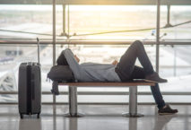 Young Asian man with suitcase luggage and backpack lying on bench in airport terminal